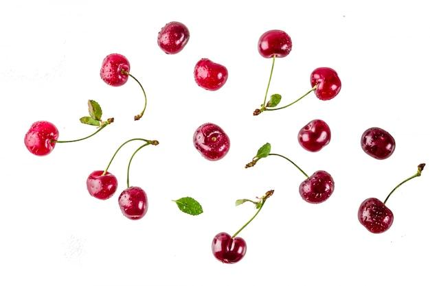 Surowa świeża wiśnia z wodą opuszcza prostego wzór odizolowywającego na białym tle