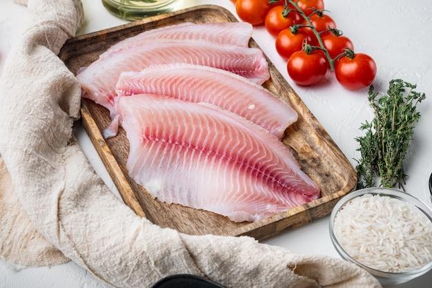 Surowa tilapia z białej ryby, z ryżem basmati i składnikami z pomidorków koktajlowych, na białym tle