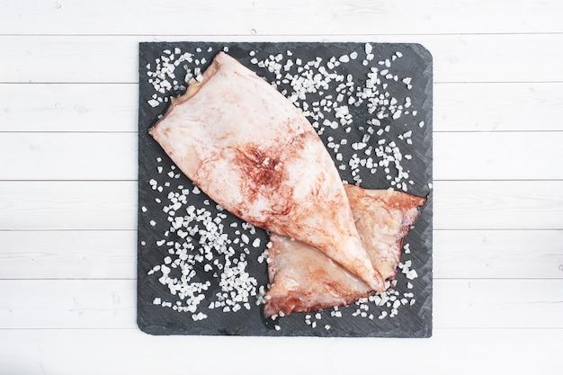 Surowa tusza kalmara z przyprawami i grubą solą na czarnej desce łupkowej. kopia przestrzeń widok z góry.