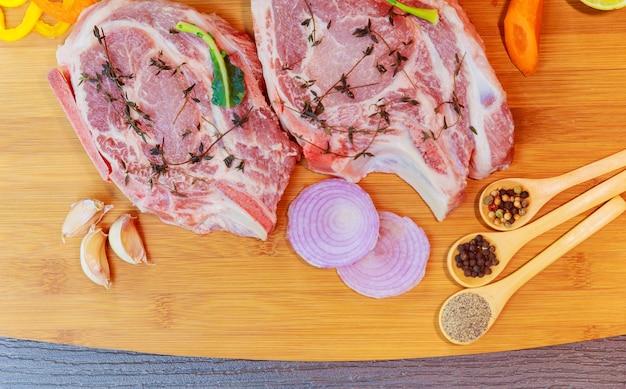 Surowa wieprzowina w marynacie, na desce do krojenia z gałązką pomidorów, nóż do granicy mięsa i przypraw, umieść tekst drewniane rustykalne tło widok z góry