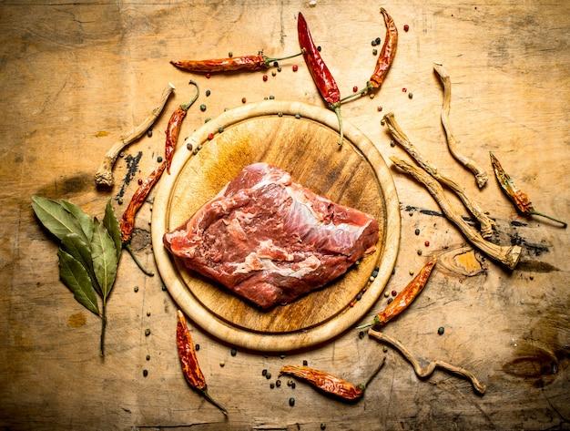 Surowa wieprzowina z przyprawami i liśćmi laurowymi. na drewnianym tle.