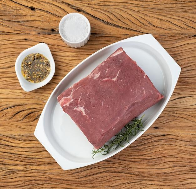Surowa wołowina ancho, typowy argentyński krój, na białym talerzu z przyprawami.