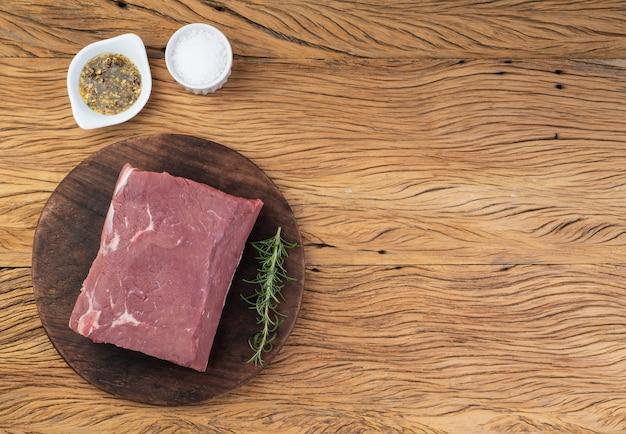 Surowa wołowina ancho, typowy argentyński krój, na drewnianej desce z przyprawami i miejscem na kopię.