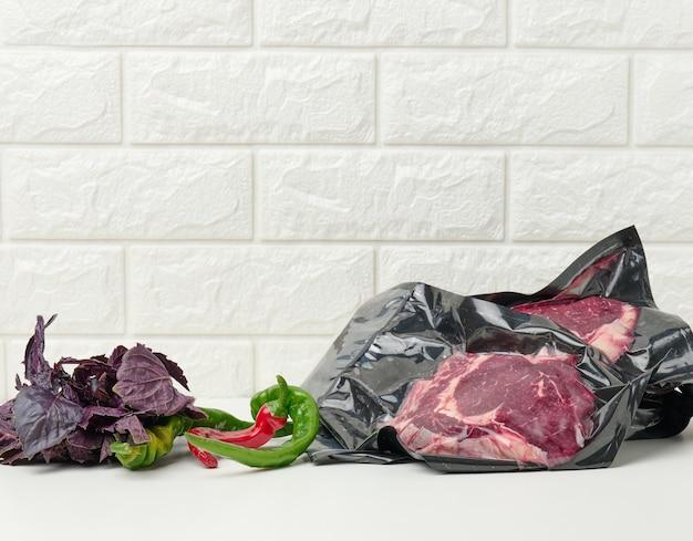 Surowa wołowina pakowana próżniowo, papryczki chili, pęczek bazylii na stole abelom