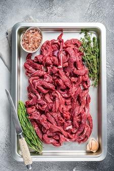 Surowa wołowina pokrojona w plastry na tacy kuchennej z rozmarynem i tymiankiem. białe tło. widok z góry.