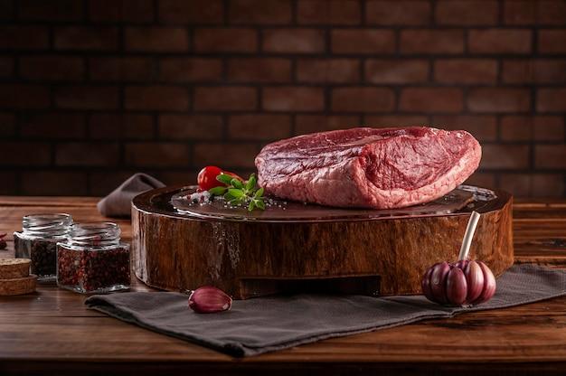 Surowa wołowina rumszkowa (brazylijska picanha) na desce do krojenia żywicowanej drewnem z przyprawami. drewniany stół z cegły ściany tło.