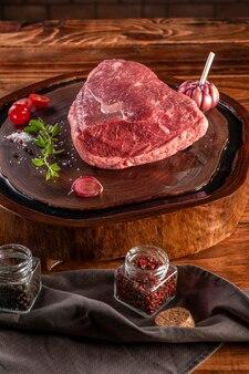 Surowa wołowina rumszkowa (brazylijska picanha) na desce do krojenia żywicowanej drewnem z przyprawami. drewniany stół.