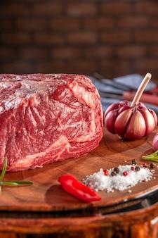 Surowa wołowina z antrykotu na desce do krojenia drewna z przyprawami na tle ściany cegieł - zbliżenie.