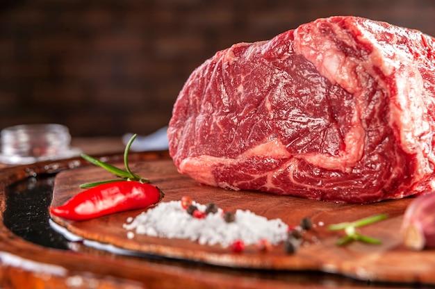 Surowa wołowina z antrykotu na desce do krojenia drewna z przyprawami - zbliżenie.