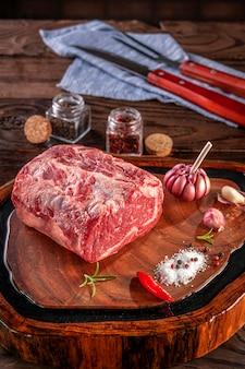 Surowa wołowina z antrykotu na drewnianej desce do krojenia z przyprawami.