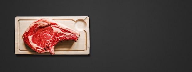 Surowa wołowina żeberka i drewniana deska do krojenia na białym na czarnym tle. widok z góry. baner poziomy