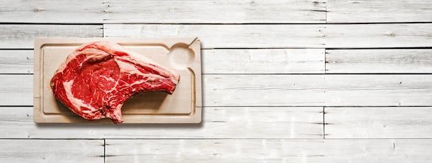 Surowa wołowina żeberka i drewniana deska do krojenia na białym tle drewnianych. widok z góry. baner poziomy