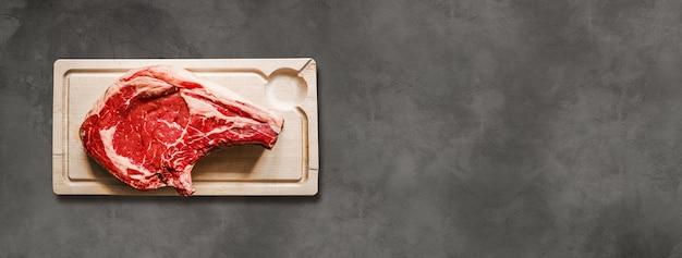 Surowa wołowina żeberka i drewniana deska do krojenia na białym tle na ciemnym tle betonu. poziomy baner
