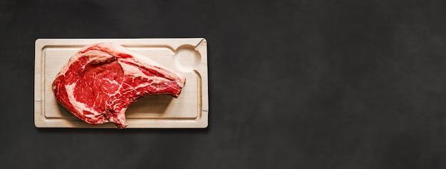 Surowa wołowina żeberka i drewniana deska do krojenia na białym tle na czarnym tle betonu. widok z góry. baner poziomy