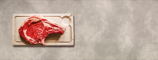 Surowa wołowina żeberka i drewniana deska do krojenia na białym tle na jasnym tle betonu. widok z góry. baner poziomy