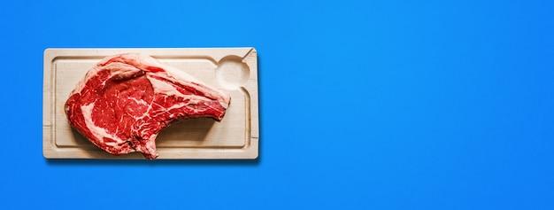 Surowa wołowina żeberka i drewniana deska do krojenia na białym tle na niebieskim tle. widok z góry. baner poziomy