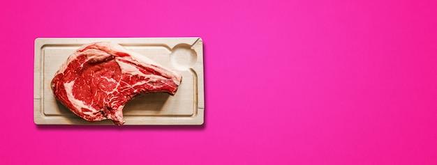 Surowa wołowina żeberka i drewniana deska do krojenia na białym tle na różowym tle. widok z góry. baner poziomy