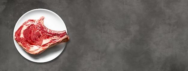 Surowa wołowina żeberka i płyta na białym tle na ciemnym tle betonu. widok z góry. baner poziomy