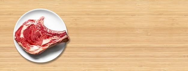 Surowa wołowina żeberka i płyta na białym tle na drewniane tła. widok z góry. baner poziomy
