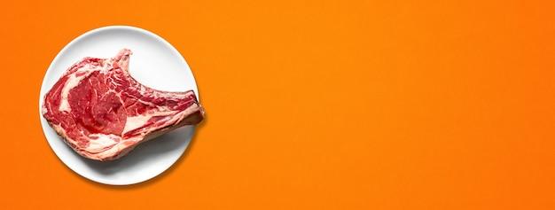 Surowa wołowina żeberka i płyta na białym tle na pomarańczowym tle. widok z góry. baner poziomy