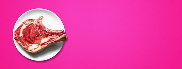 Surowa wołowina żeberka i płyta na białym tle na różowym tle. widok z góry. baner poziomy