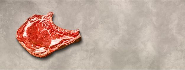 Surowa wołowina żeberka na białym tle na jasnym tle betonu. widok z góry. baner poziomy