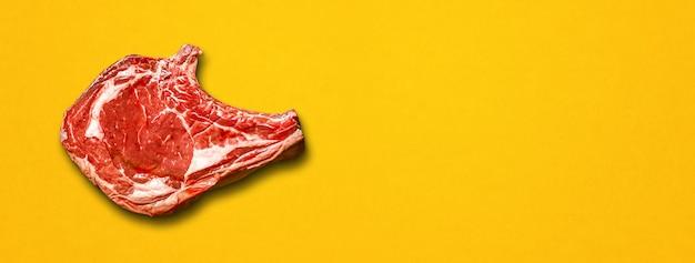 Surowa wołowina żeberka na białym tle na żółtym tle. widok z góry. baner poziomy