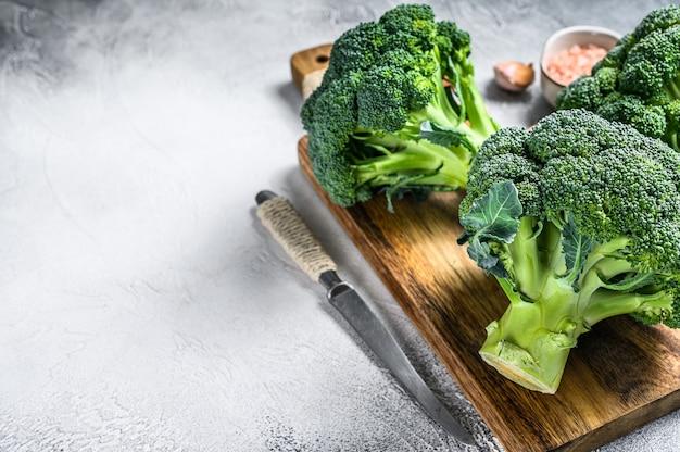 Surowa zielona kapusta brokułowa na drewnianej desce do krojenia. białe tło. widok z góry. skopiuj miejsce.