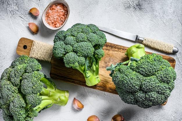 Surowa zielona kapusta brokułowa na drewnianej desce do krojenia