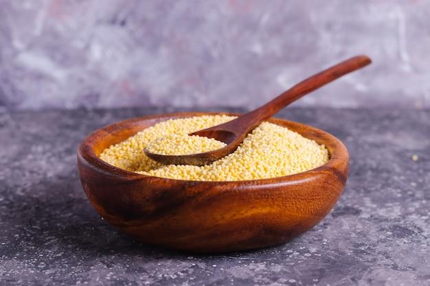 Surowa żółta jagła dla właściwego odżywiania i zdrowie w drewnianym talerzu na szarym tle
