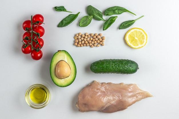 Surowce do dietetycznej sałatki z kurczakiem, pomidorem z ogórkiem awokado i szpinakiem