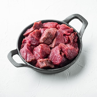 Surowce na gulasz. zestaw świeżej, surowej siekanej wołowiny na żeliwnej patelni, na białej kamiennej powierzchni, kwadratowy format