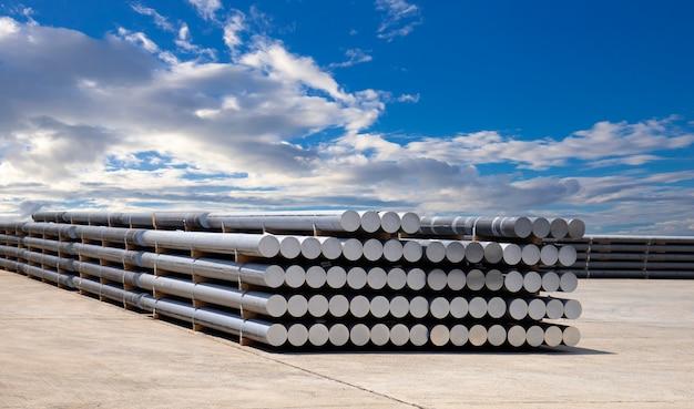 Surowce przemysłowe, sterty prętów aluminiowych w fabryce profili aluminiowych