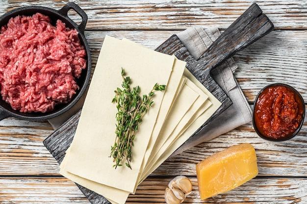 Surowe arkusze lasagne i inne składniki. białe drewniane tło. widok z góry.