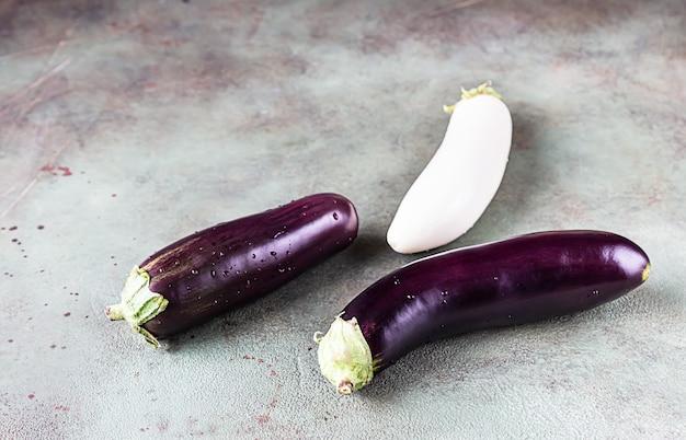 Surowe bakłażany fioletowo-białe, solanum melongena lub bakłażany z kroplą wody. skopiuj miejsce.