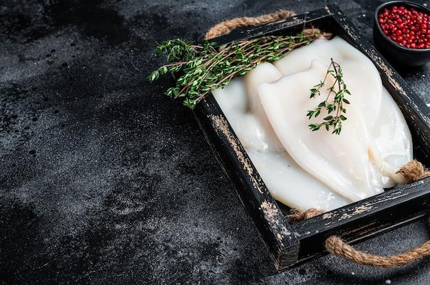 Surowe białe kalmary lub kalmary na drewnianej tacy z ziołami