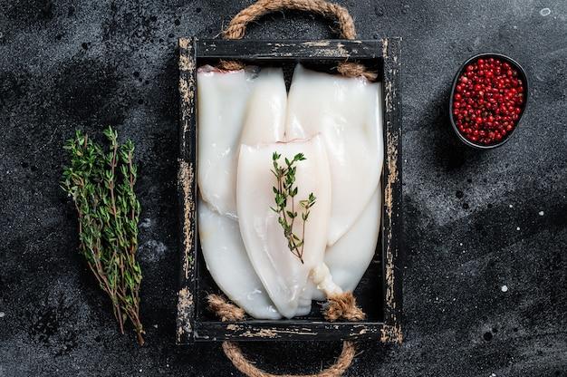 Surowe białe kalmary lub kalmary w drewnianej tacy z ziołami. czarne tło. widok z góry.