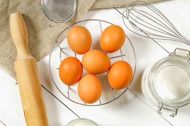 Surowe brązowe jaja kurze, mleko, cukier, mąka, trzepaczka, wałek do ciasta