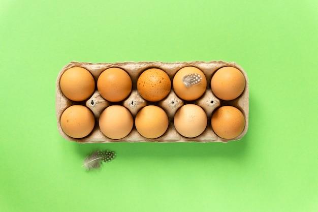 Surowe brązowe jaja kurze w tekturowym pudełku na zielonym tle, widok z góry.