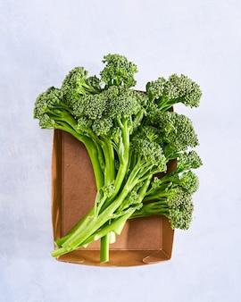 Surowe brokuły, świeże organiczne brokuły różyczki zielone, młode brokuły warzywne w papierowym pudełku.