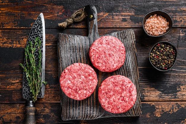Surowe burgery stekowe paszteciki z mieloną wołowiną i tymiankiem na drewnianej desce do krojenia