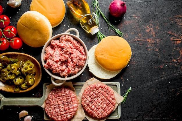 Surowe burgery z mieloną wołowiną, oliwą, bułeczkami i pomidorami. na ciemnym tle rustykalnym