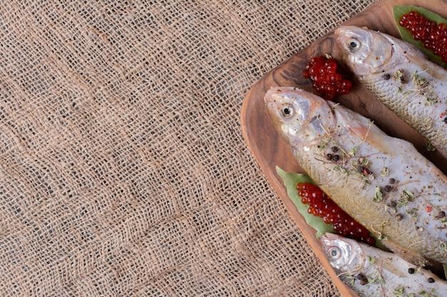 Surowe całe ryby z czerwonym kawiorem na desce.
