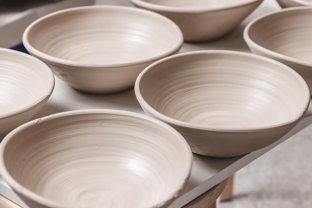 Surowe ceramiczne miski wykonane z białej gliny na kole garncarskim czekają na wprowadzenie do pieca garncarskiego, koncepcja pracy ręcznej, kreatywności i sztuki, pionowe zdjęcie
