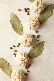 Surowe chinkali, pieprz i liście laurowe na białym tle z teksturą