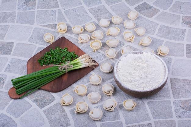 Surowe ciasta chinkali na mące z pęczkiem zielonej cebuli.