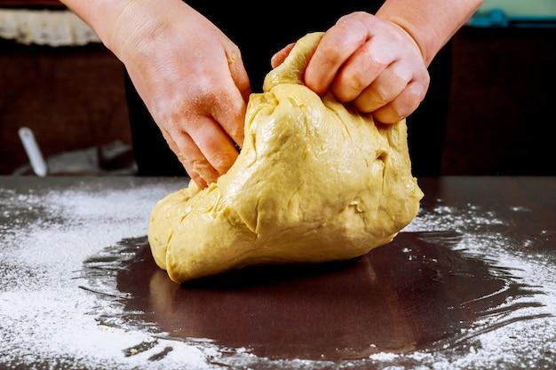 Surowe ciasto do pizzy w rękach szefa kuchni