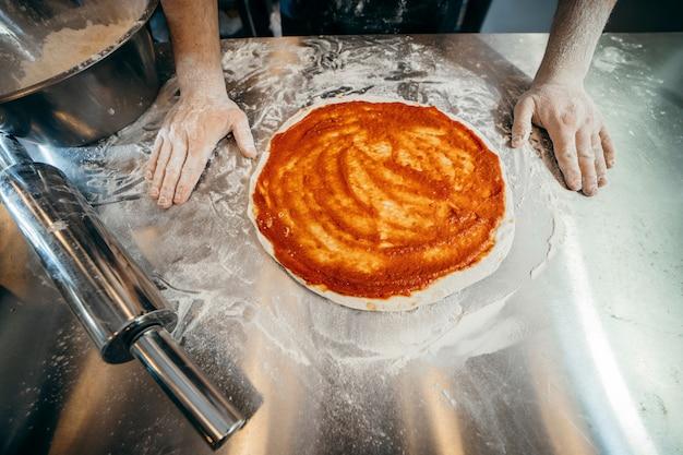 Surowe ciasto do przygotowania pizzy ze składnikiem: sos pomidorowy, mozzarella, pomidory,