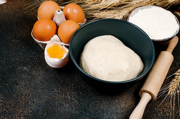 Surowe ciasto drożdżowe w misce i składniki, jajka, mąka, kłosy pszenicy na ciemnym stole, koncepcja piekarni