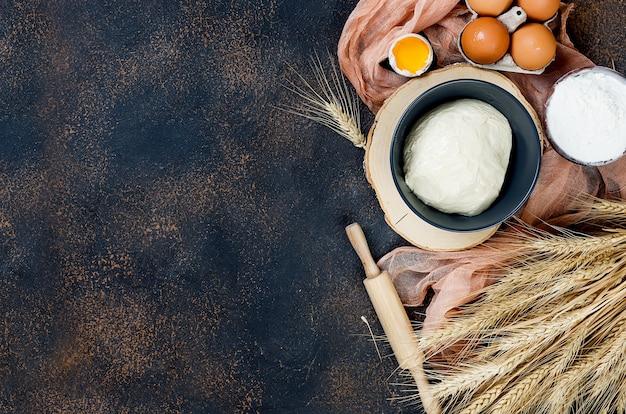 Surowe ciasto drożdżowe w misce i składniki, jajka, mąka, kłosy pszenicy na ciemnym stole kuchennym,